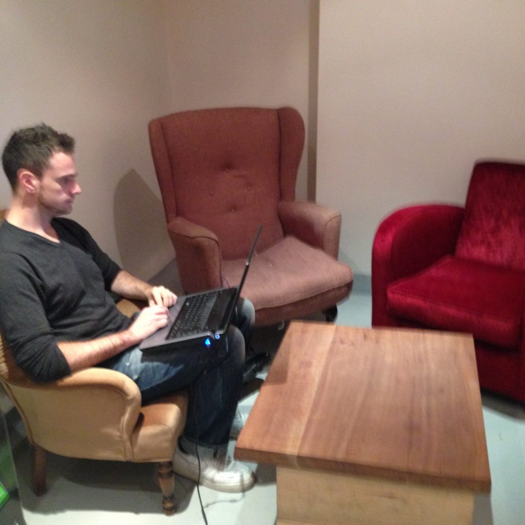 Assorted armchairs and a man working on a laptop perched on his knees