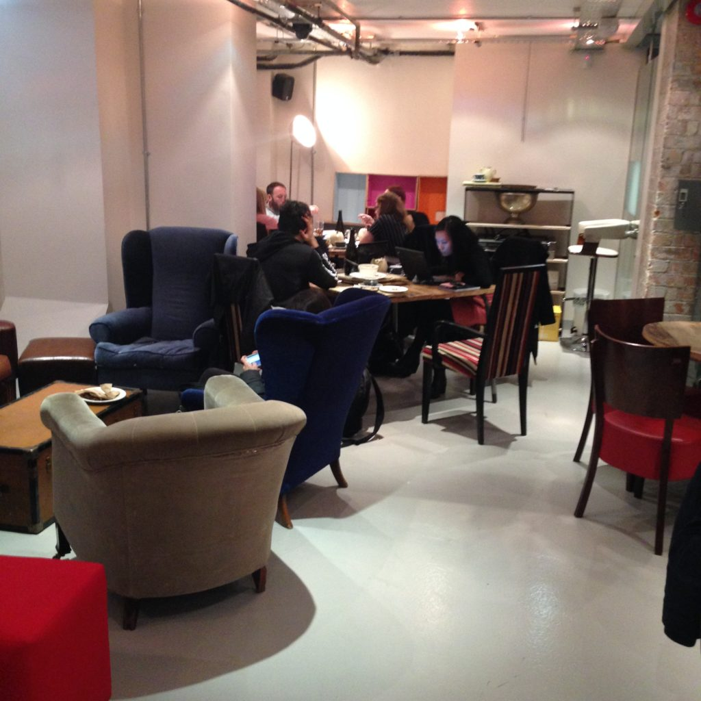 Assorted armchairs, and tables where two students sit together working quietly, and a group of four are collaborating.