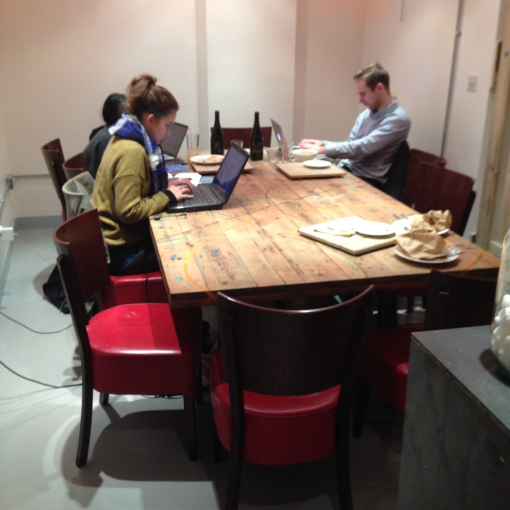 A communal table fowhere three people are working independently.