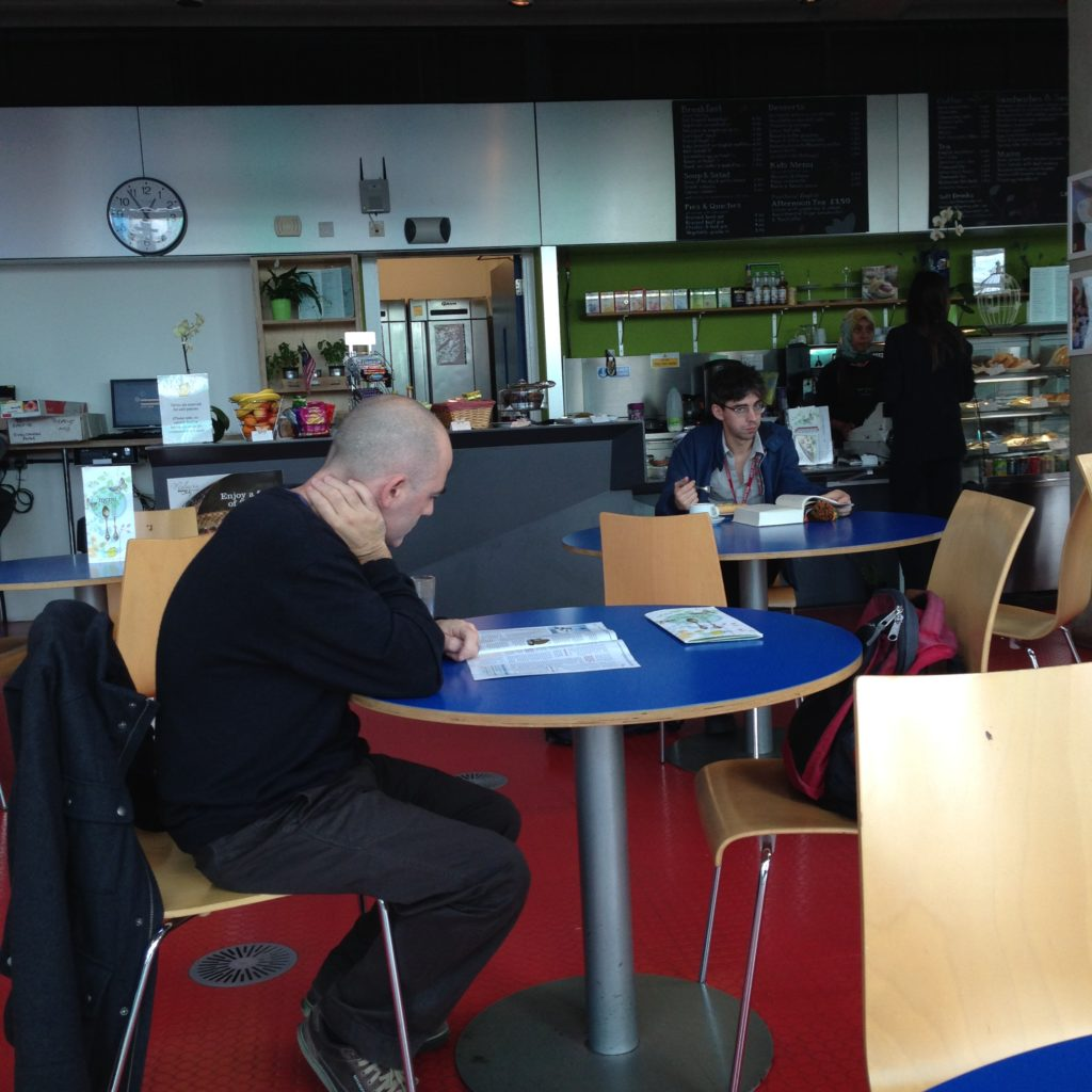 Library cafe with round tables and people reading